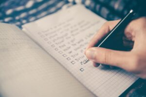 Person writing list in journal