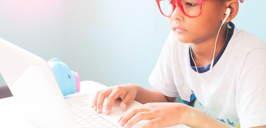 Little boy child wearing red glasses listening and using laptop computer