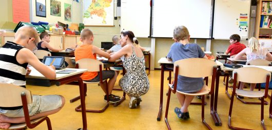 teacher working with a young student in a classroom