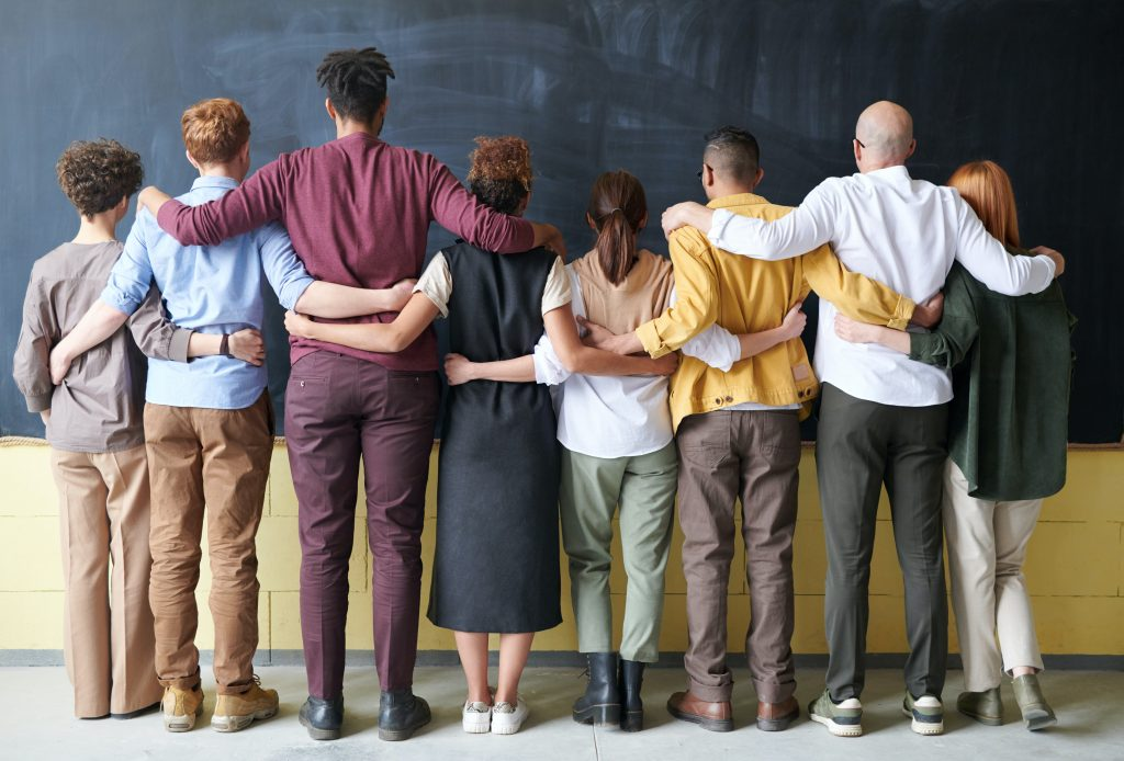 A group of people joined together facing a chalkboard