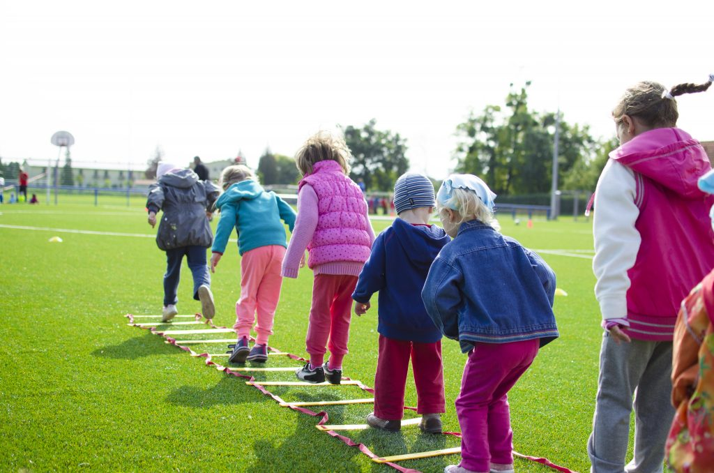 Kids in a line engaging in a jumping competition outside