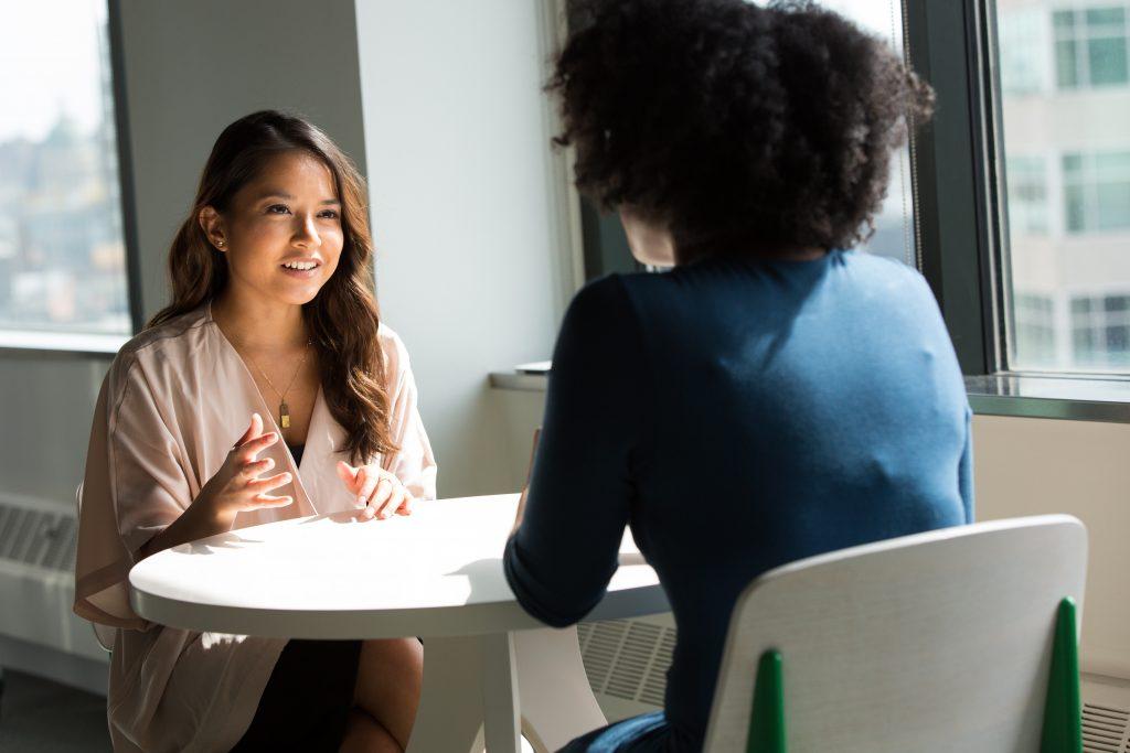 Two women talking across a table