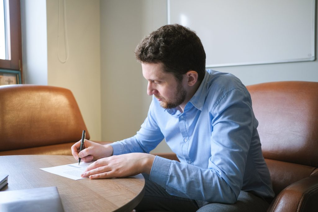 Man writing on a piece of paper while sitting at his desk
