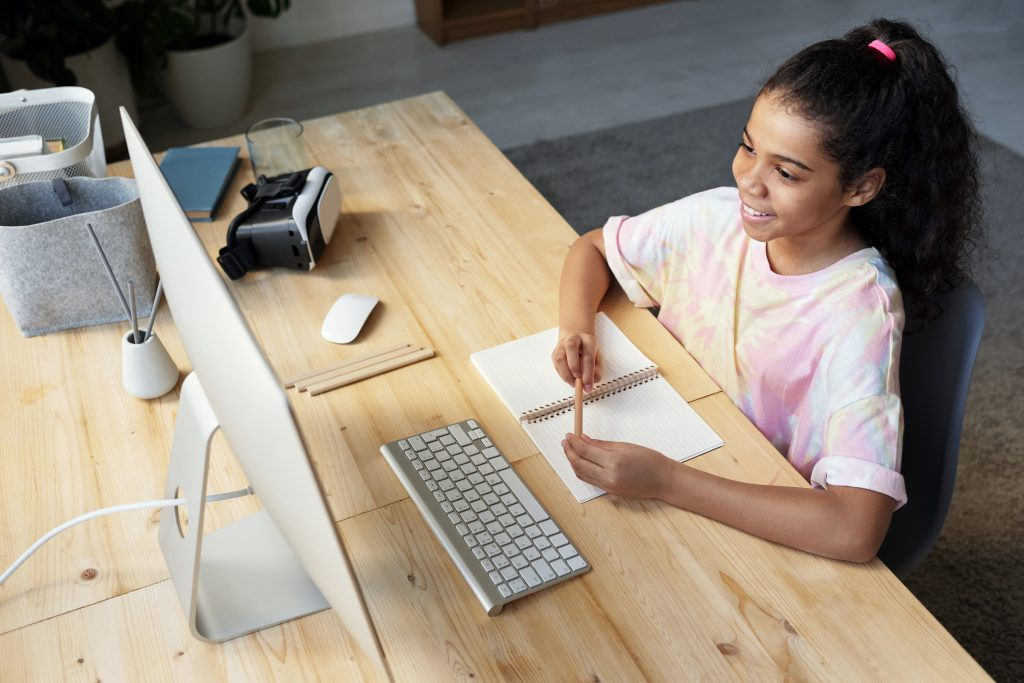 A student wearing a pink tie-dye t-shirt smiles while looking at a computer screen