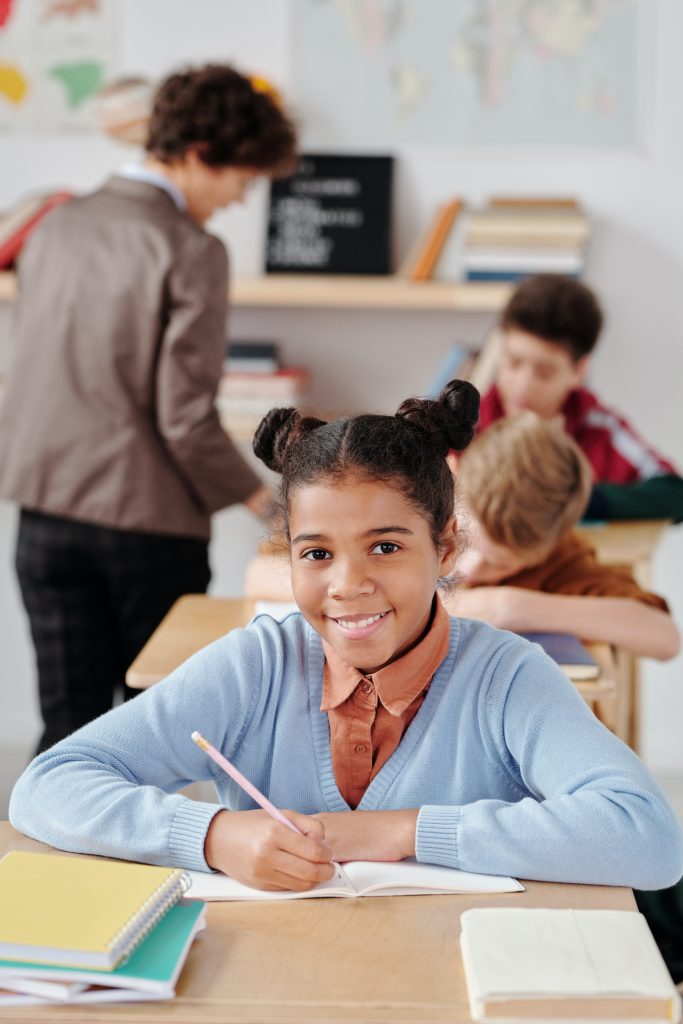 Young girl in long sleeve sweater sitting at desk with pencil in hand smiling while teacher helps students in the background