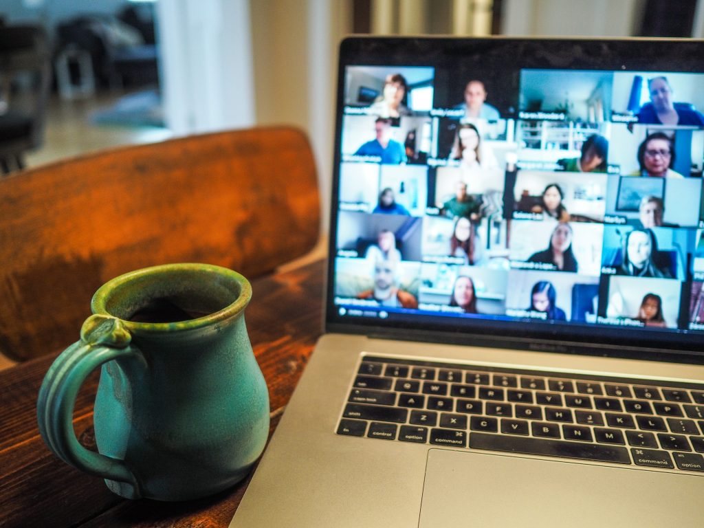 Laptop displaying group of people in grid view during a Zoom meeting, with a coffee mug sitting on the table nearby.