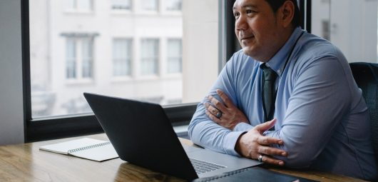 Man sitting at office desk with laptop open in front of him