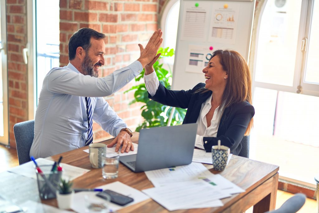 Man and woman high five while sitting at a table with papers spread in front of them