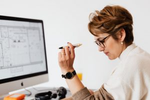 Woman sitting at desk in front of computer with pen in hand thinking