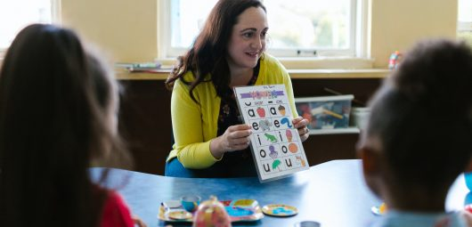 teacher sitting at table with two children teaching vowels