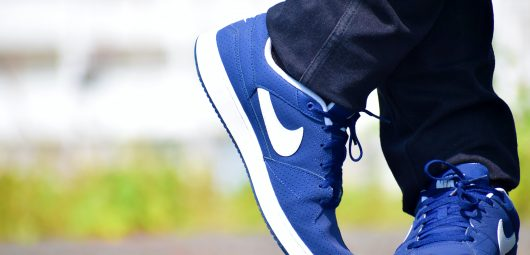 close up of feet wearing blue Nike shoes