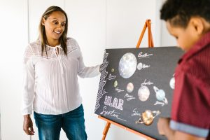 Teacher looking at a student's solar system diagram